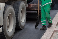 Workman with shovel working on new asphalt Stock Image