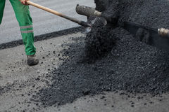 Workman with shovel working on new asphalt Stock Photo