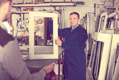 Workman showing PVC manufacturing output. Glad careful adult workman showing PVC manufacturing output in workshop Royalty Free Stock Images