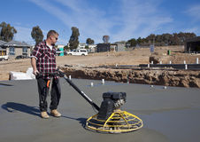 Workman smoothing newly poured concrete. Workman using 'helicopter' concrete smoothing machine on newly poured flooring at housing estate Royalty Free Stock Image