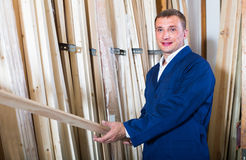 Workman standing with wooden plank Royalty Free Stock Photography