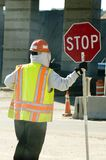 Workman and Stop Sign. Standing construction work wearing yellow and orange reflective vest and hardhat holding upright red stop sign Stock Images