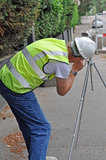 Workman surveying road. A Workman surveying road with survey equipment in hi vis jacket and hard hat Royalty Free Stock Photos