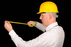 Workman with tape measure. Half body side view of workman wearing yellow helmet using tape measure, isolated on black background Royalty Free Stock Photo