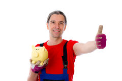 Workman with thumb up is showing a piggy bank. Young workman with thumb up is showing a piggy bank Stock Photo
