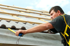 Workman tiling roof. Middle aged workman measuring first row of roof tiles on building with tape measure Stock Photo