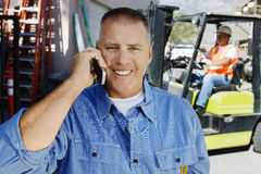 Workman Using Cell Phone. Portrait of a happy male industrial worker using cell phone with coworker in the background Stock Photography