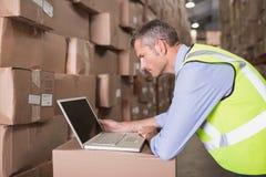 Workman using laptop at warehouse Stock Photo