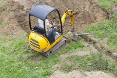 Workman using a mini digger to dig a hole for a swimming pool. Workman using a mini digger to excavate a hole for a swimming pool in a garden lawn with green royalty free stock image