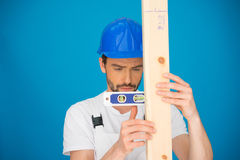 Workman using a spirit level. Handsome young workman in a hardhat using a spirit level holding it horizontally against a plank of wood against a blue background Royalty Free Stock Images