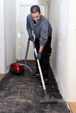 Workman vacuuming a passage during renovations Stock Image