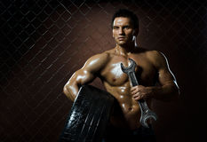 Workman. The very muscular workman with rubber-tire and big wrench,  on  netting  steel fence background Royalty Free Stock Photo