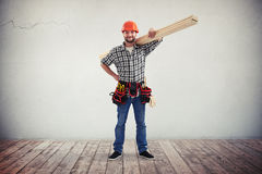 A workman with wooden boards on his shoulder. A young bearded workman in casual clothes, hard hat and utility belt is holding some wooden boards on his shoulder royalty free stock photos