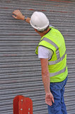 Workman working on metal roller door Stock Photos