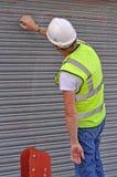 Workman working on metal roller door. In hi vis jacket and hard hat Stock Photos