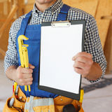 Workman with wrench and contract Royalty Free Stock Photos