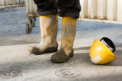 Workmans muddy boots and helmet Royalty Free Stock Photography