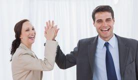 Workmates alegres que fazem a elevação cinco Imagem de Stock