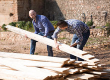 Workmen arranging building timber at farm Royalty Free Stock Images