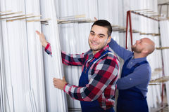 Workmen choosing PVC window profile Royalty Free Stock Images