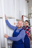 Workmen choosing PVC window profile Royalty Free Stock Image