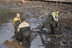 Workmen clearing the lake of f. Ish before it gets dredged Stock Image