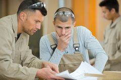 Workmen in duscussion while contemplating plans stock image