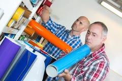 Workmen examining rolls coloured vinyl stock photo