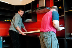 Workmen fitting kitchen. Two middle aged workmen fitting or installing unit top in modern kitchen royalty free stock photography