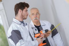 Workmen holding tape measure and cordless drill. Workman Royalty Free Stock Photography