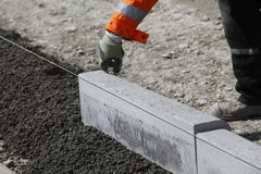 Workmen laying curbstones. Closeup of workmen laying curbstones for a new sidewalk at a construction site Stock Photography