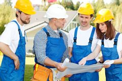 Workmen looking at house design Stock Photography