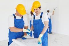 Workmen looking at house design Stock Photos