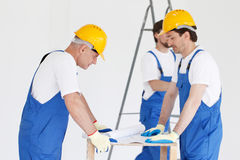 Workmen looking at house design Royalty Free Stock Photography