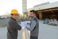 Workmen looking at plans on worksite stock images