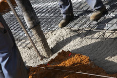 Workmen pouring cement for foundations Stock Images