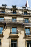 Workmen on ropes on old residential building front, Paris. Royalty Free Stock Photos