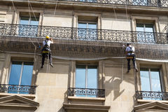 Workmen on ropes on old residential building front, Paris. Royalty Free Stock Images