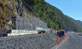 Workmen rush to complete Roadside Barrier Prior to road Opening. Royalty Free Stock Photos