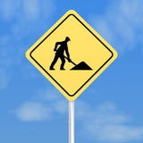 Workmen traffic sign. Closeup of diamond shaped yellow workmen sign with blue sky background Stock Photo