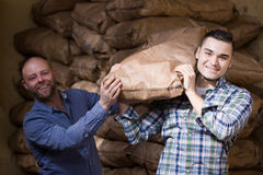 Workmen unloading shed with coal bags Royalty Free Stock Photos