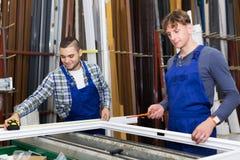 Workmen working with window profiles Royalty Free Stock Photo