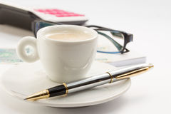 Workong environment white table or place with cup of coffee glasses pen calculator and money Stock Photos
