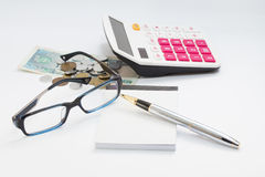 Workong environment white table or place with glasses pen calculator and money Royalty Free Stock Images