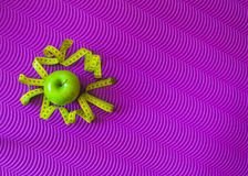 Workout και ικανότητα Η έννοια ενός healithy τρόπου ζωής Πράσινο μήλο και μέτρηση της ταινίας σε ένα χαλί για την ικανότητα στοκ εικόνα