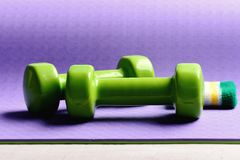Workout και αθλητισμός Barbells κοντά στην άσπρη και πράσινη ζώνη χεριών στοκ φωτογραφία