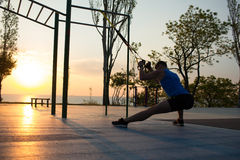 workout με τα λουριά αναστολής στην υπαίθρια γυμναστική, την ισχυρή κατάρτιση ατόμων νωρίς το πρωί στο πάρκο, την ανατολή ή το ηλ στοκ φωτογραφία