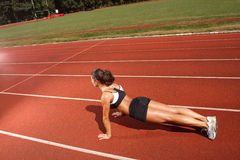 Workout. Athletic woman working out on track Stock Images