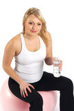 After the Workout. Pretty young woman sitting on an exercise ball, drinking from a bottle of water Royalty Free Stock Photo