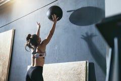 workout Addestramento della donna di sport con la palla di Crossfit alla palestra immagini stock libere da diritti